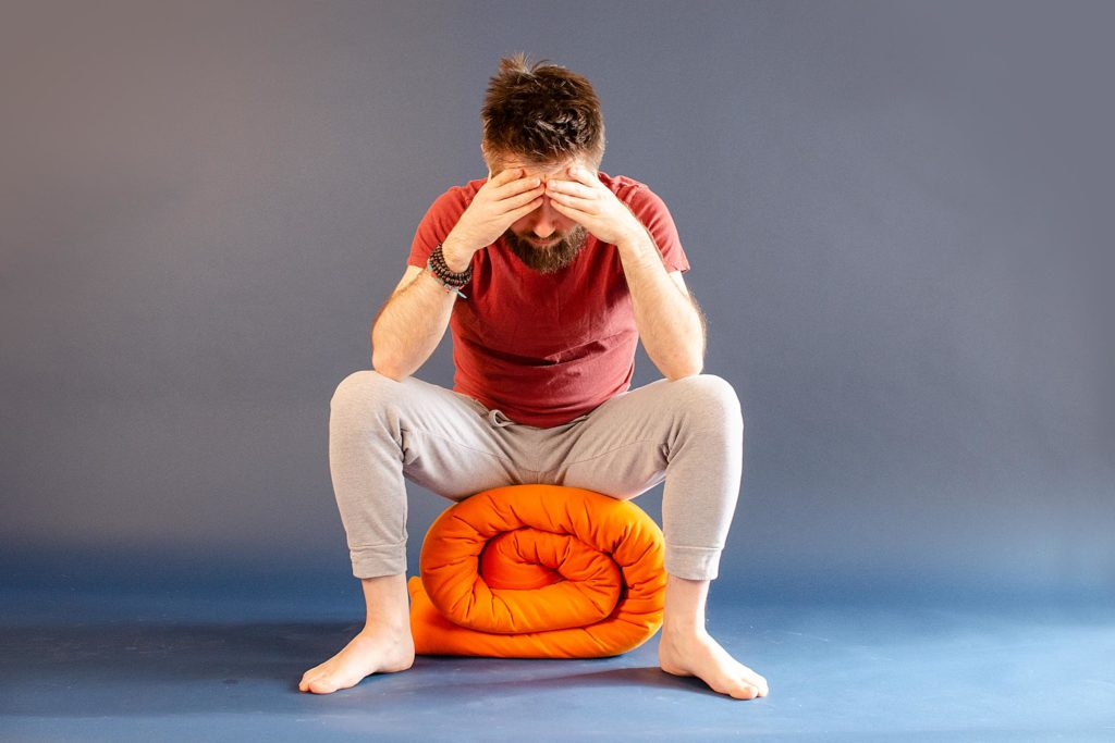 Man practicing nada yoga a technique that benefits concentration.