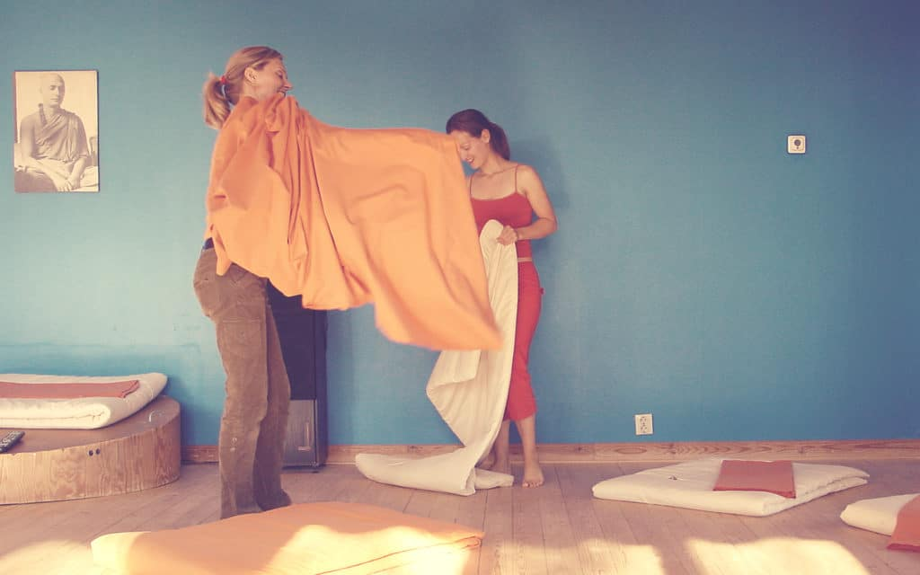 Vigyana Shakti and Padma Shakti changing yoga mat covers at Haa course center.