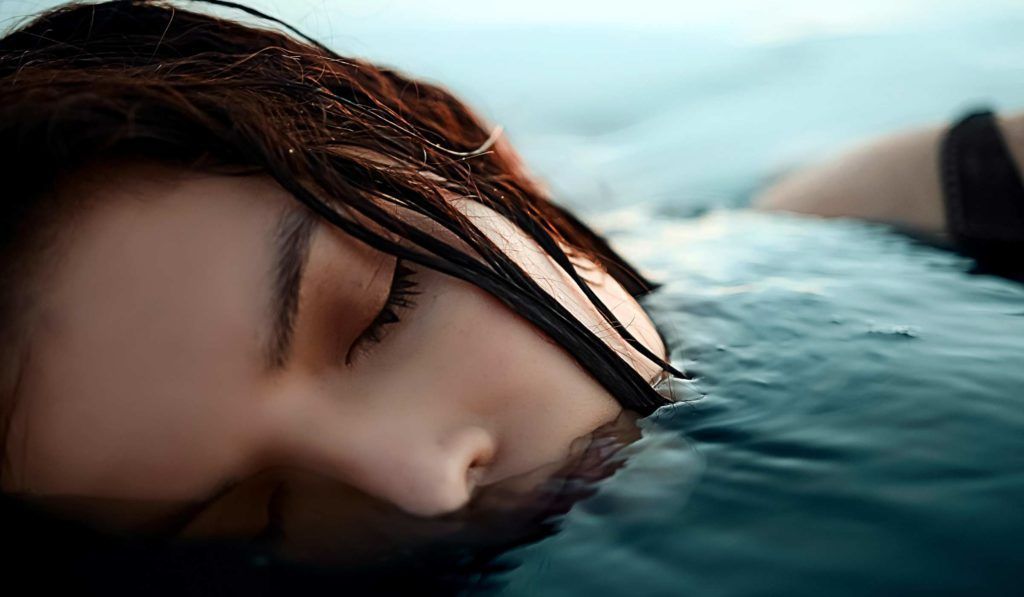 Image of a woman in water. Symbolic illustration of falling asleep and losing yourself in the unconscious.