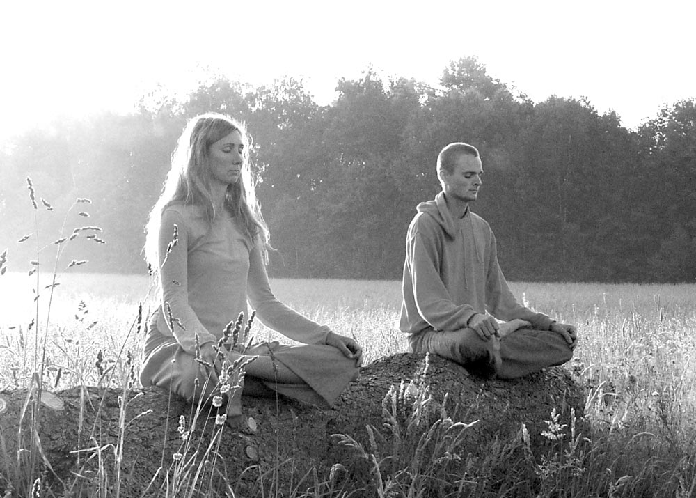 Man and woman sitting in the lotus pose.