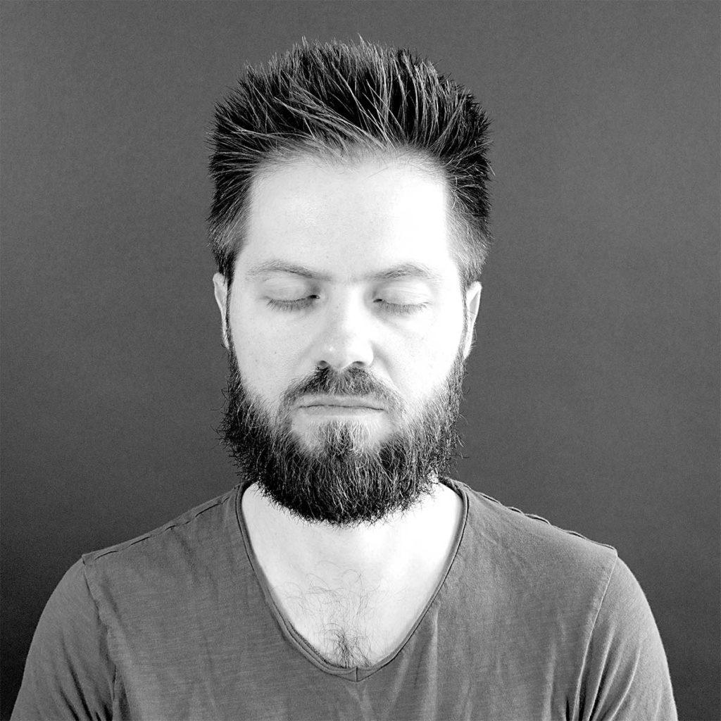 Young man with beard meditating.