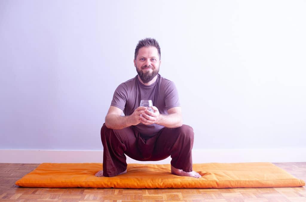 Man sitting in the squatting pose during shankhaprakshalana.